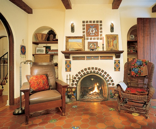 caption: Ronstadt's study, nestled between the entrance hall and a guest room, features original tile work around and above the fireplace. A Native American beaded bag hangs at left, near a signed William Morris chair. The paintings on the mantel are by Maynard Dixon.